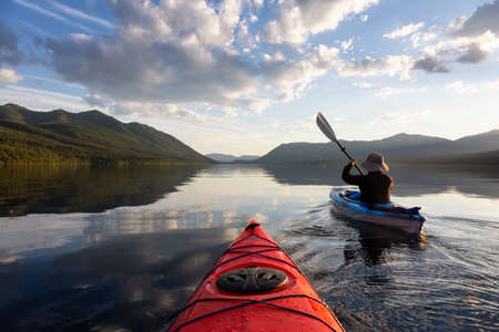 Photo pour Adventurous Man Kayaking in Lake McDonald during a sunny summer evening with American Rocky Mountains in the background. Taken in Glacier National Park, Montana, USA. - image libre de droit