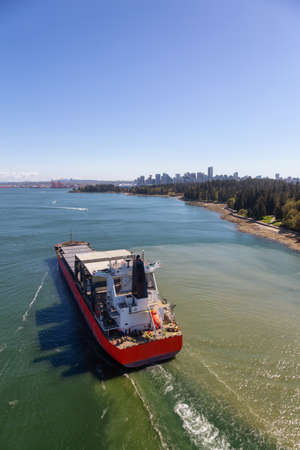 Aerial View of a Big Container Ship passing by Stanley Park with Downtown City in the Background. Taken from Lions Gate Bridge, Vancouver, British Columbia, Canada.