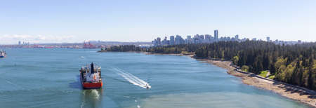 Aerial Panoramic View of a Big Container Ship passing by Stanley Park with Downtown City in the Background. Taken from Lions Gate Bridge, Vancouver, British Columbia, Canada.