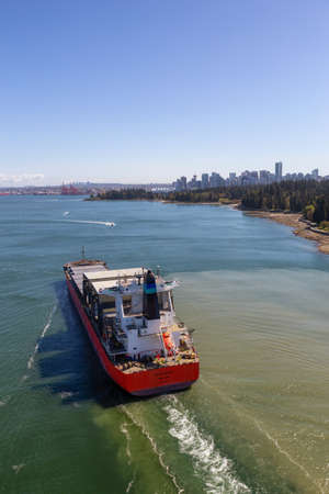 Vancouver, British Columbia, Canada - April 20, 2019: Aerial View of a Big Container Ship passing by Stanley Park with Downtown City in the Background.