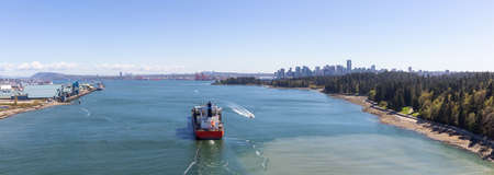 Vancouver, British Columbia, Canada - April 20, 2019: Aerial Panoramic View of a Big Container Ship passing by Stanley Park with Downtown City in the Background.