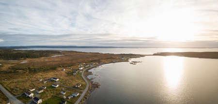 Photo pour Aerial panoramic view of a small town on a rocky Atlantic Ocean Coast during a cloudy sunset. Taken in Raleigh, Newfoundland, Canada. - image libre de droit