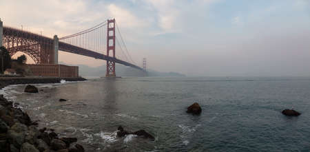 Beautiful panoramic view of Golden Gate Bridge during a cloudy sunset. Taken in San Francisco, California, United States.