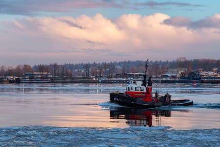 Industrial Tugboat pulling a load in Fraser River during a colorful winter sunset with ice in the water. Taken in New Westminster, Vancouver, BC, Canada.
