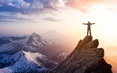 Photo pour Adventure, Explore and Lifestyle Concept Composite. Adventurous Man Hiker With Hands Up on top of a Steep Rocky Cliff. Sunset or Sunrise. Landscape Taken from Washington, USA. - image libre de droit