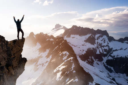 Photo pour Fantasy Adventure Composite with a Man on top of a Mountain Cliff with Dramatic Landscape in Background during Sunset or Sunrise. Landscape from British Columbia, Canada. - image libre de droit