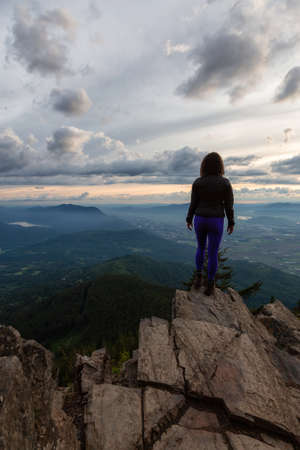 Photo for Adventurous Girl on top of a Rocky Mountain overlooking the beautiful Canadian Nature Landscape during a dramatic Sunset. Taken in Chilliwack, East of Vancouver, British Columbia, Canada. - Royalty Free Image