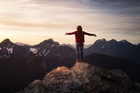 Photo pour Fantasy Adventure Composite with a Girl on top of a Rock Cliff with Beautiful Nature in Background during Sunset or Sunrise. Landscape from British Columbia, Canada. Concept: Hike, Freedom, Journey - image libre de droit