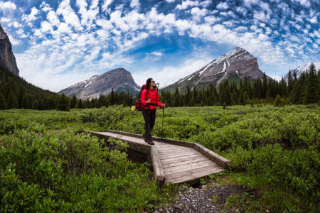 Photo for Female Backpacker Hiking in Canadian Rockies. Colorful Blue Sky Art Render. Taken near Banff, boarder of British Columbia and Alberta, Canada. Concept: Explore, Adventure, Trekking, Backpacking - Royalty Free Image