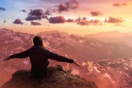 Foto de Adventurous Man with Open Hands is taking in the momen on top of a mountain. Fantasy Composite. Sunset or Sunrise Sky. Landscape from British Columbia, Canada. - Imagen libre de derechos