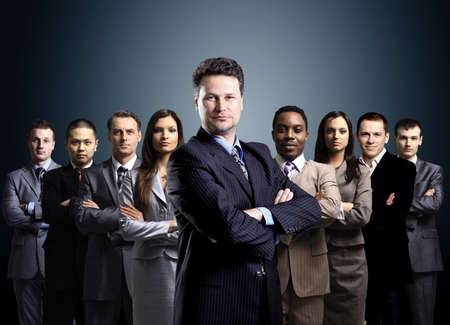 business team formed of young businessmen standing over a dark background の写真素材