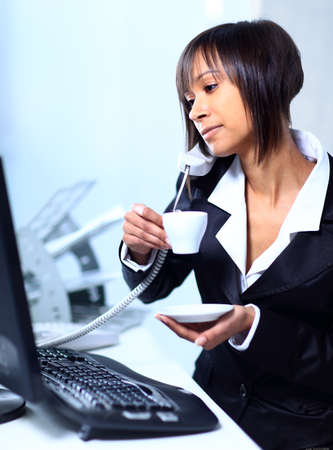 Businesswoman sitting at the table in office lobby, drinking coffee.