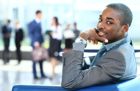 Foto de Portrait of smiling African American business man with executives working in background - Imagen libre de derechos