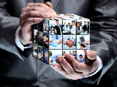 man holding abstract cube with business imagesの写真素材