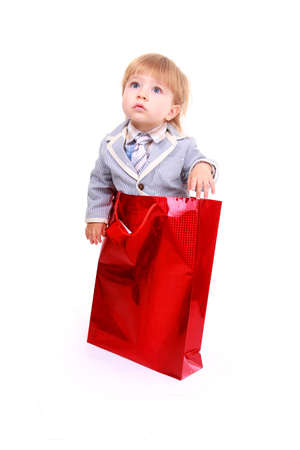 Portrait of cute boy on shopping bag isolated on white background