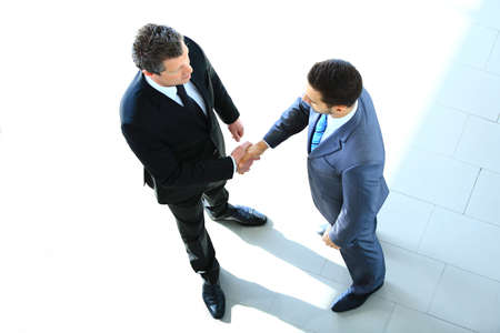 Top view of a two businessman shaking hands - Welcome to businessの写真素材