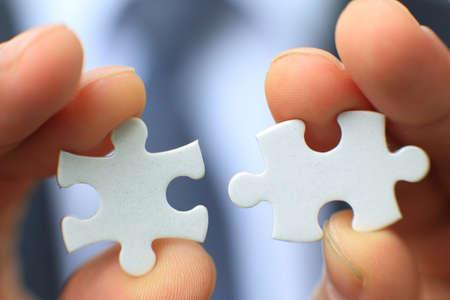 Foto de Businessman holding two blank white puzzle pieces in his hands conceptual of solving a problem, growth and development. - Imagen libre de derechos