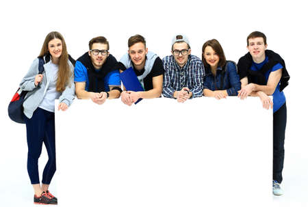 Photo pour Full length portrait of confident college students displaying blank billboard against white background - image libre de droit