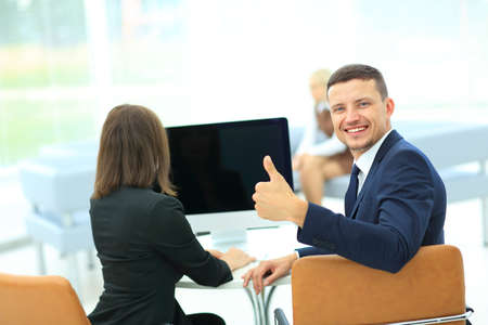 Business partners working on computer at modern office and showing  thumb