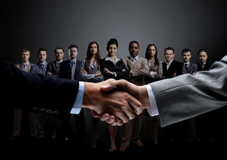 closeup of handshake of business partners on the background of a professional business team on a dark background.the photo has a empty space for your textの写真素材