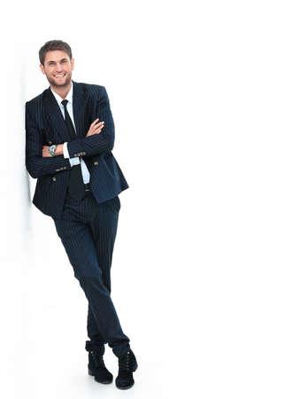Photo pour Portrait of a handsome young man in a business suit. standing near the wall - image libre de droit