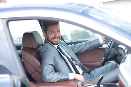 Portrait of a handsome successful business man driving his car
