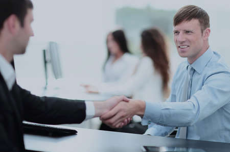Business handshake. Two business people shaking hands in office.