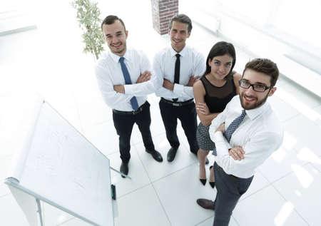 business team standing beside a blank flipchart