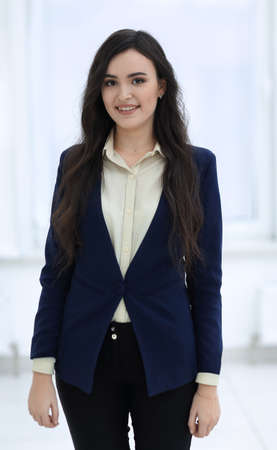 Attractive smiling young business woman in an office.