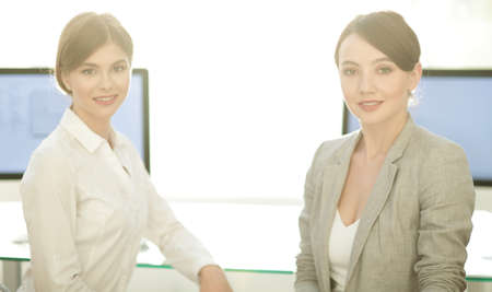 portrait of two business women on the background of the workplace.