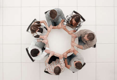 top view.The business team hold hands, forming a circle
