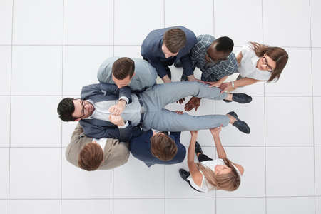 top view.a fun business team is rocking their leader