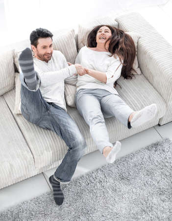 Photo pour laughing couple having fun on the couch in the living room - image libre de droit