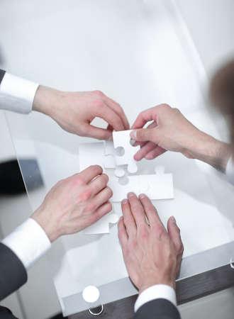 Photo pour close up.business partners solving the puzzle - image libre de droit