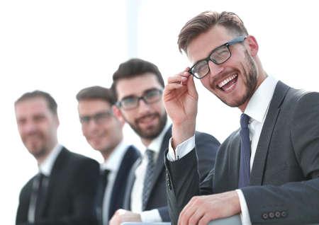 Photo pour close up.smiling businessman sitting on the background of colleagues - image libre de droit