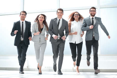 Photo pour in full growth.a group of business people walking together. - image libre de droit