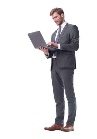 Photo pour in full growth. businessman standing with open laptop - image libre de droit