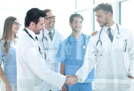 Photo pour doctors shaking hands in hospital corridor - image libre de droit
