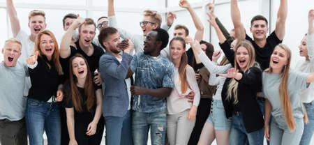 Photo pour team of happy young people showing their success - image libre de droit