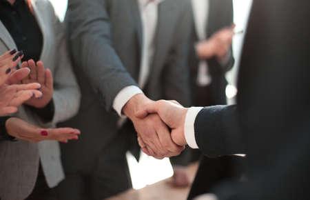 Photo pour close up. smiling businessman shaking hands with his business partner - image libre de droit