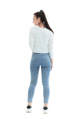 Photo pour rear view. stylish girl in jeans standing in front of a white wall. - image libre de droit