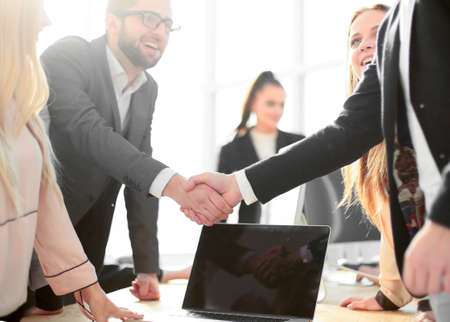 Photo for happy employees shaking hands in the workplace. - Royalty Free Image