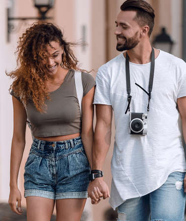 Photo for A loving couple of tourists look at each other and walking - Royalty Free Image