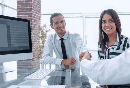 Photo pour men shaking hands and smiling while sitting at the desk - image libre de droit