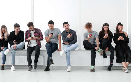 Photo pour group of casual young people with smartphones sitting in a row. - image libre de droit
