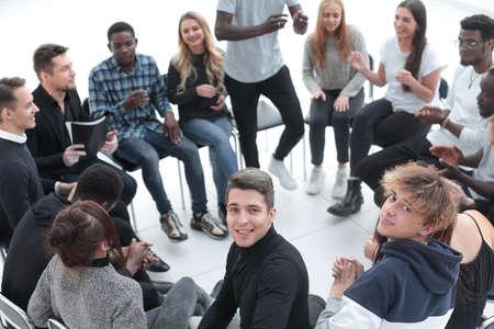 Photo pour smiling young man sitting in a circle of friends - image libre de droit