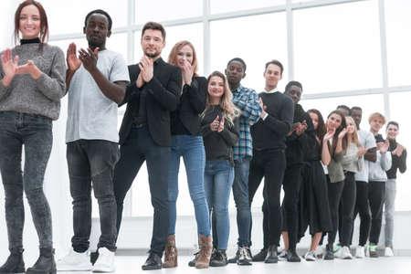 Photo pour diverse young people applaud standing in line - image libre de droit