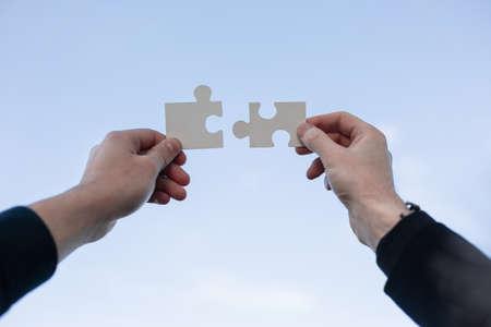 Photo pour Closeup hand connecting jigsaw puzzle with, business solutions, success and strategy concept - image libre de droit