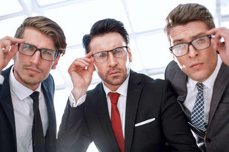 Photo pour close up.three attentive businessmen looking at the camera - image libre de droit