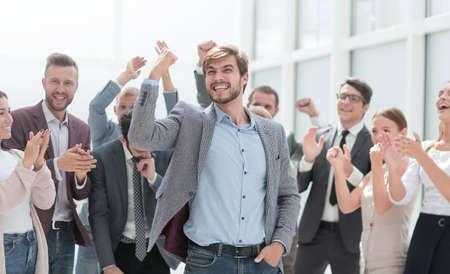 Photo pour cheerful employees congratulating a colleague on the promotion - image libre de droit